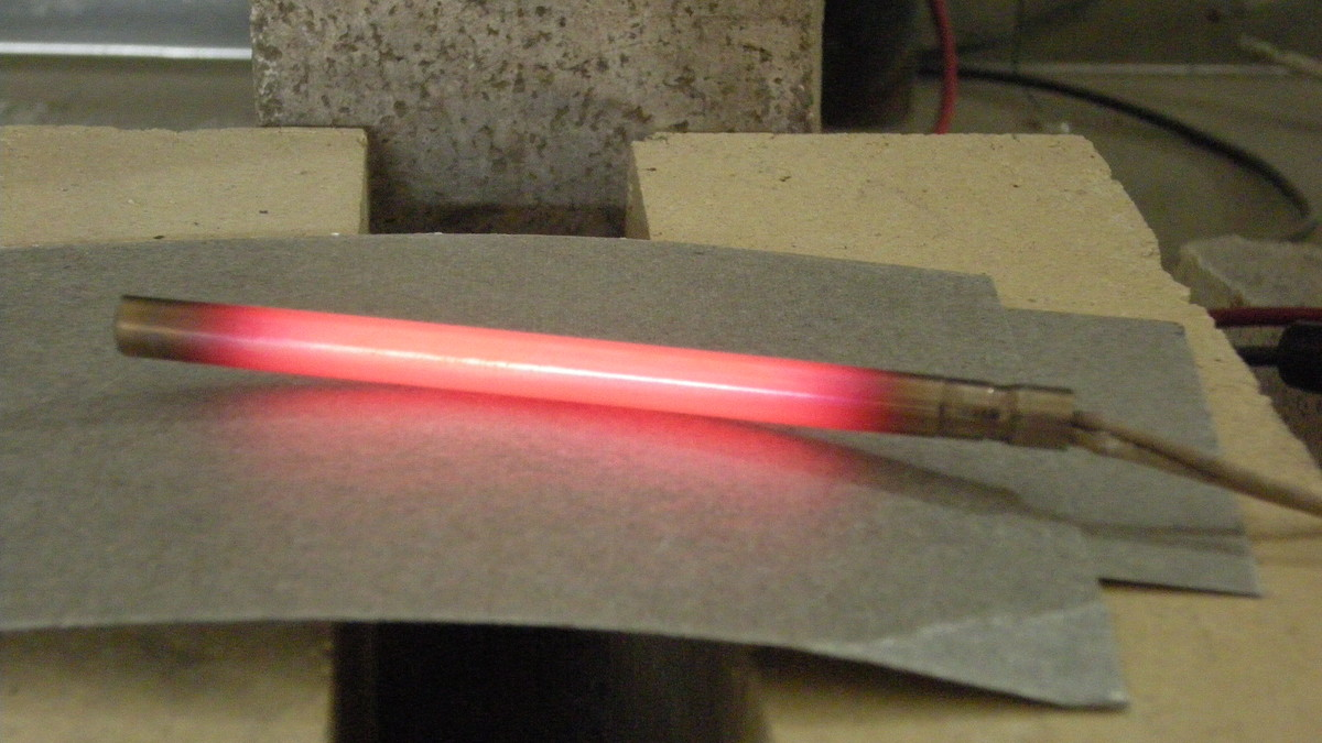 Electric current running through a cartridge heater, causing a red-hot glow due to low conductivity / high resistance.