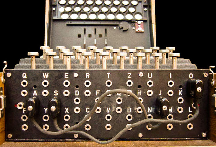 The plugboard is positioned at the front of an Enigma machine, below the keys.