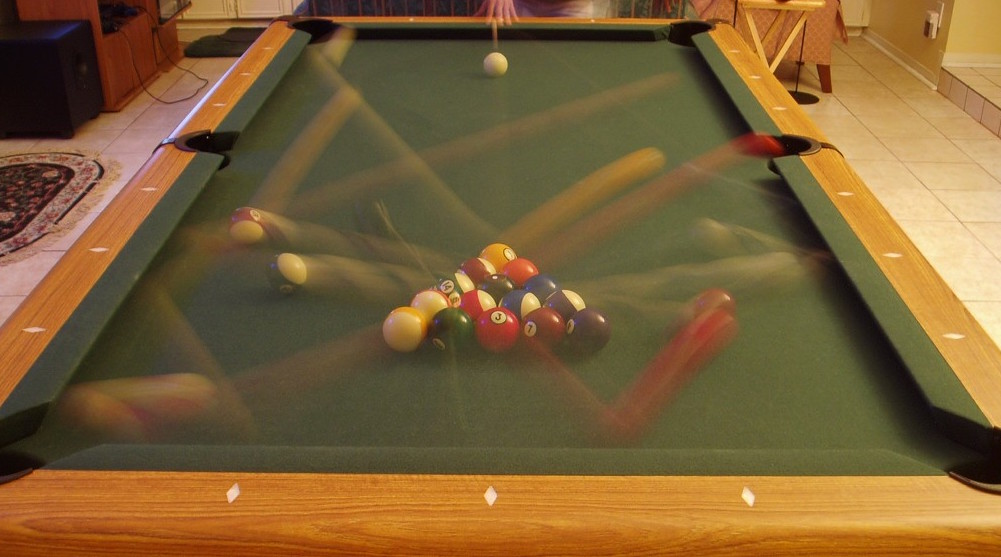 Before a game of 8-ball is started on a billiards table, the balls can only occupy one of 15 spaces within the <em>rack</em>. However, after the <em>break</em>, the balls are scattered to positions all around the table, so the <strong>entropy increases greatly</strong>.